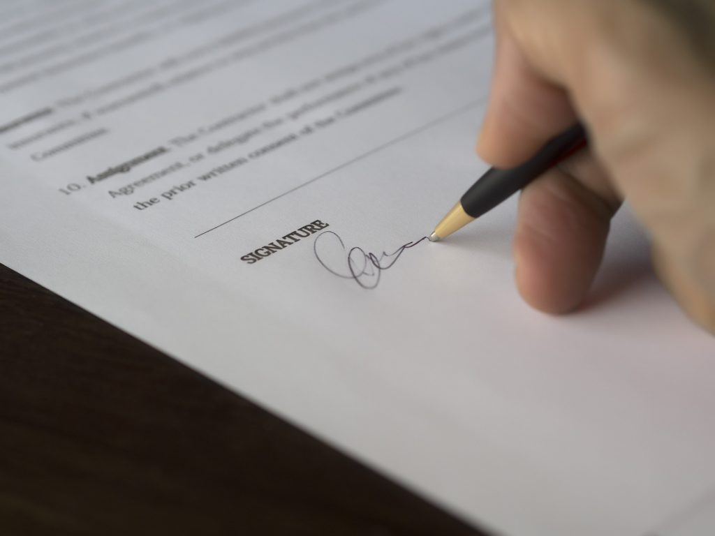 person signing on paper