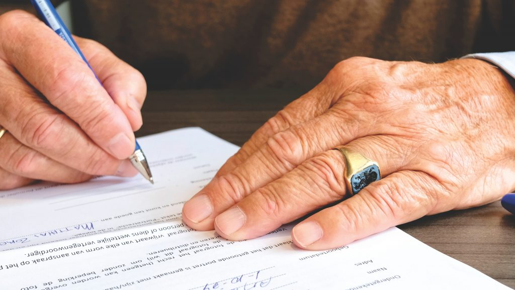man signing on a document