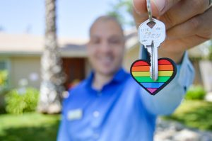 man holding a key attached to a rainbow heart keychain